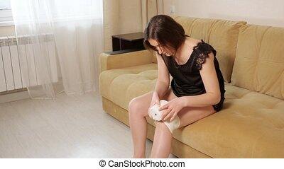 Woman wraps elastic bandage on injured knee.