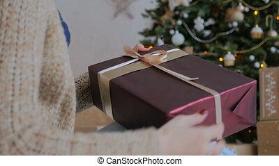 Woman wraps ribbon on christmas gift box at home. Holidays,...