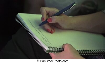 Woman write notes at conference indoors closeup