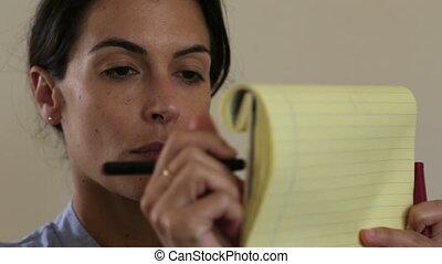 Woman write on yellow writing block - Shot of Woman write on...