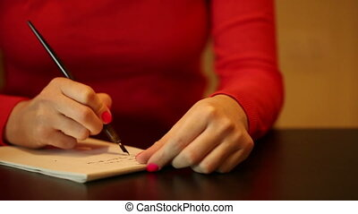Woman write something. Home scene. Camera moves before the person