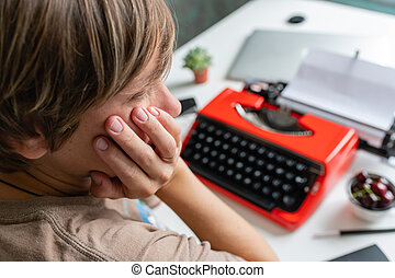 Woman writer thoughtfully working on a book on her Desk red typewriter