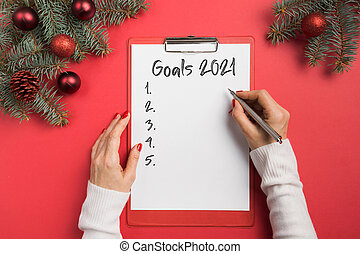 Woman writes goals, checklist, plans and dreams for New Year.