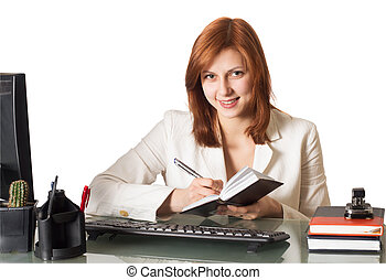 woman writes in a notebook sitting at a desk