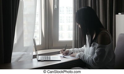 Woman writing at laptop