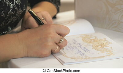 Woman writing greeting in the book of greetings