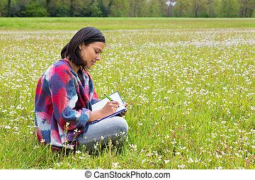 Woman writing in blooming dutch meadow