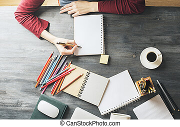 Close up of woman's hands writing in empty copybook placed on office desktop with other supplies and coffee cup. Copy space