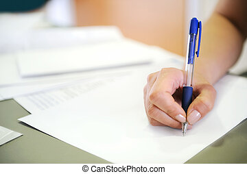 Closeup on female hand writing in blank document