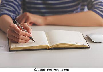 Woman writing in hardcover copybook