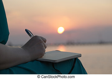 Close up view of the hand of a woman writing in her diary at sunset with the glowing orb of the sun reflected over a still ocean