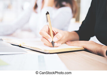 Woman writing in notepad