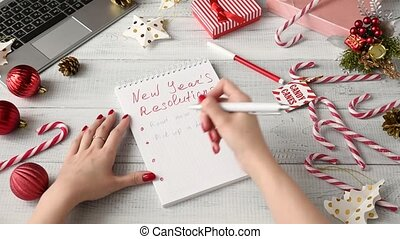 Woman writing New Year's resolutions. Hands writing goals...