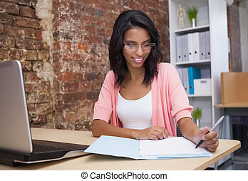 Woman writing notes with laptop