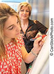 Woman writing on a flip chart