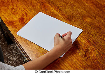 Woman writing on a sheet of papaer