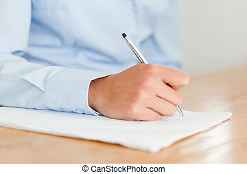 Woman writing on a sheet of paper while sitting