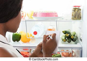 Woman Writing On Spiral Book Near Refrigerator