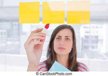Woman writing on sticky note