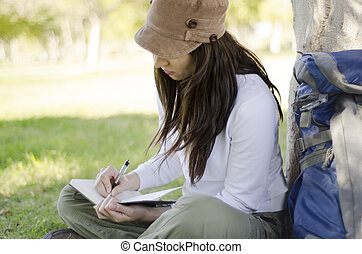 Young beautiful woman writing on travel journal on hiking trip