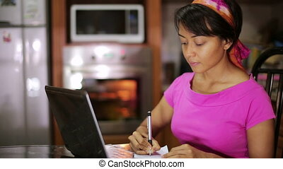 woman writing recipe from internet