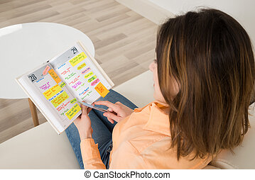 Woman Writing Schedule In Diary