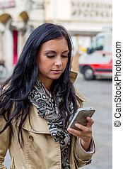 woman writing sms - a young woman writing a text message on...