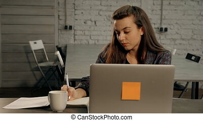 Woman writing text in agenda and working in office -...