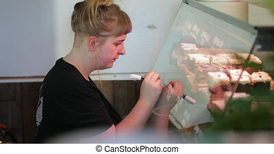 Woman Writing the Prices of Cakes on the Glass - Woman...