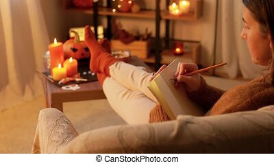 people, holidays and leisure concept - young woman with pencil writing to diary and resting her feet on table at cozy home