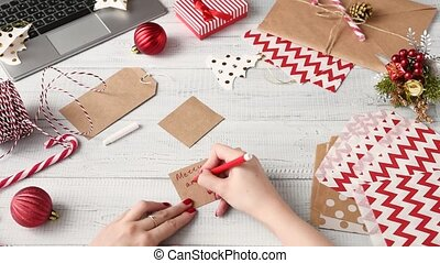 Woman writing with a red marker wishes Merry Christmas and...