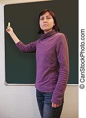 Woman writing with chalk on blackboard