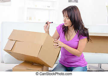 woman writing with pen on shipping box