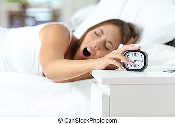 Woman yawning at wakeup turning off alarm clock