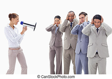 Woman yelling through a megaphone at business people with their hands on their ears against white background