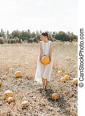 woman yellow pumpkin holds hands subject Halloween