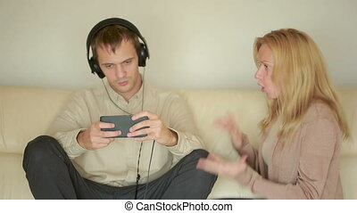 woman yells at man with headphones. Husband plays on the smartphone