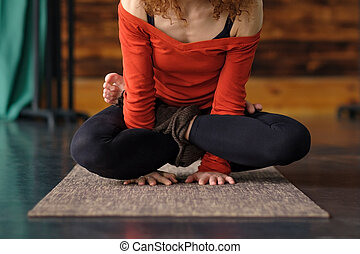 woman yoga instructor doing Cock Pose or Rooster, Kukkutasana asana