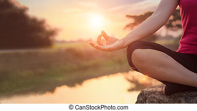 Woman yoga practicing and meditating by the lake in summer background
