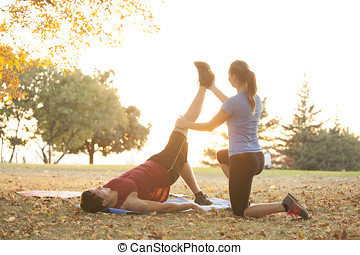 Woman yoga trainer demonstrating to student different...