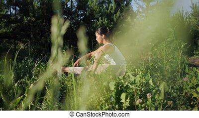 Woman yogi on a gym mat. Camera movement among grass