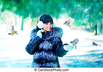 Woman Young girl feeding birds in the winter landscape