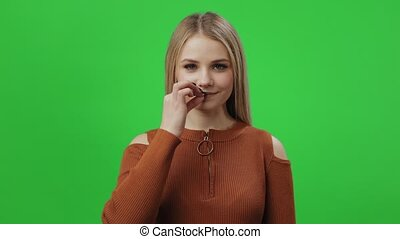 Beautiful young woman wearing eyeglasses and casual brown sweater zipping her lips with fingers. Isolated over chroma key background. Concept of secret and silence.