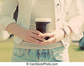 Woman's hands holding coffee cup outdoors.