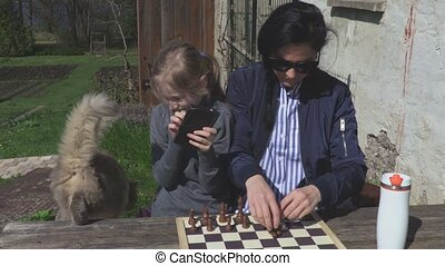 Woman,daughter and cat near chess board