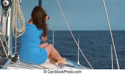 Womanin a blue dress sits aboard the yacht and exploring the horizon through binoculars
