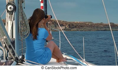 Womanin a blue dress sits aboard the yacht and exploring the horizon through binoculars. Slow motion