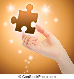Womanish hand with a orange shining piece of puzzle