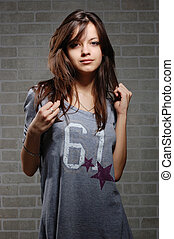 womanly brunette on brick wall background . Casual dress...