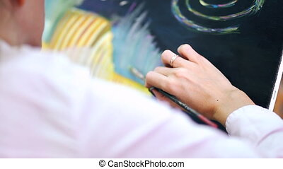 Woman's artist hands drawing picture with oil paints on...